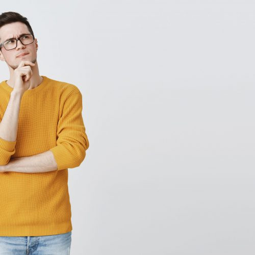 Hmm what if. Smart and thoughtful good-looking guy in geek glasses and cozy yellow sweater holding hand on chin, frowning and looking at upper right corner as thinking, making decision or assumption. Body language concept